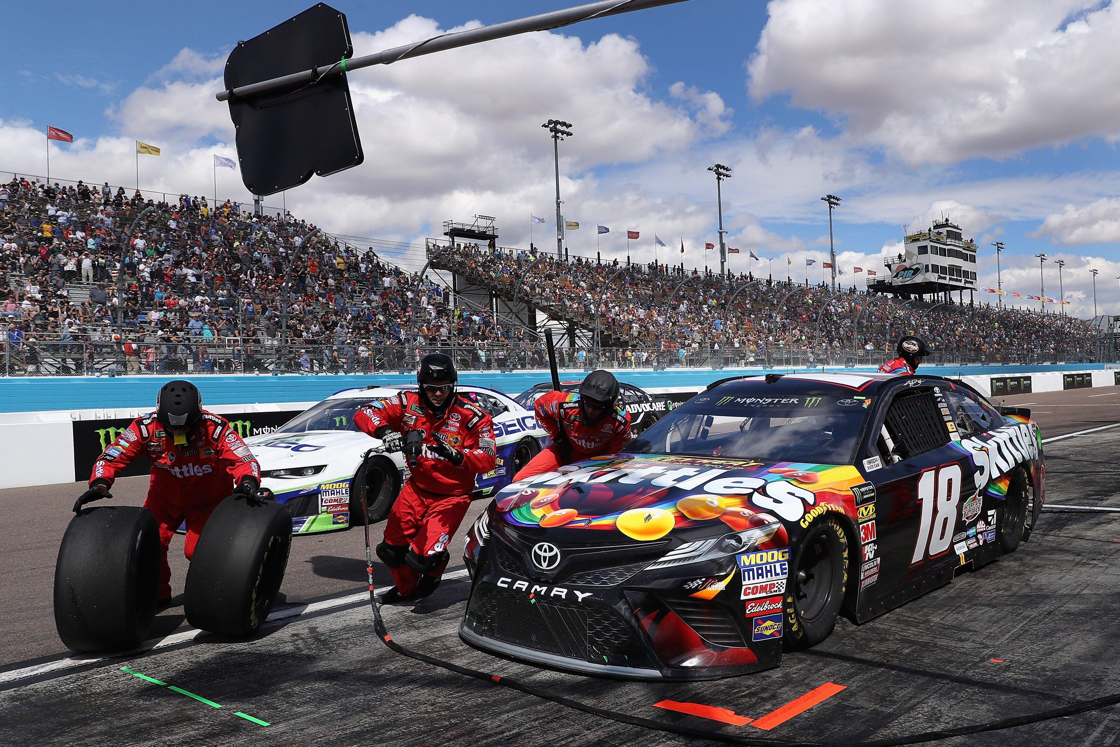 Kyle Busch on pit road - Joe Gibbs Racing crew members - ISM Raceway