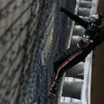 Noah Gragson climbs the fence after the win at Kansas Speedway