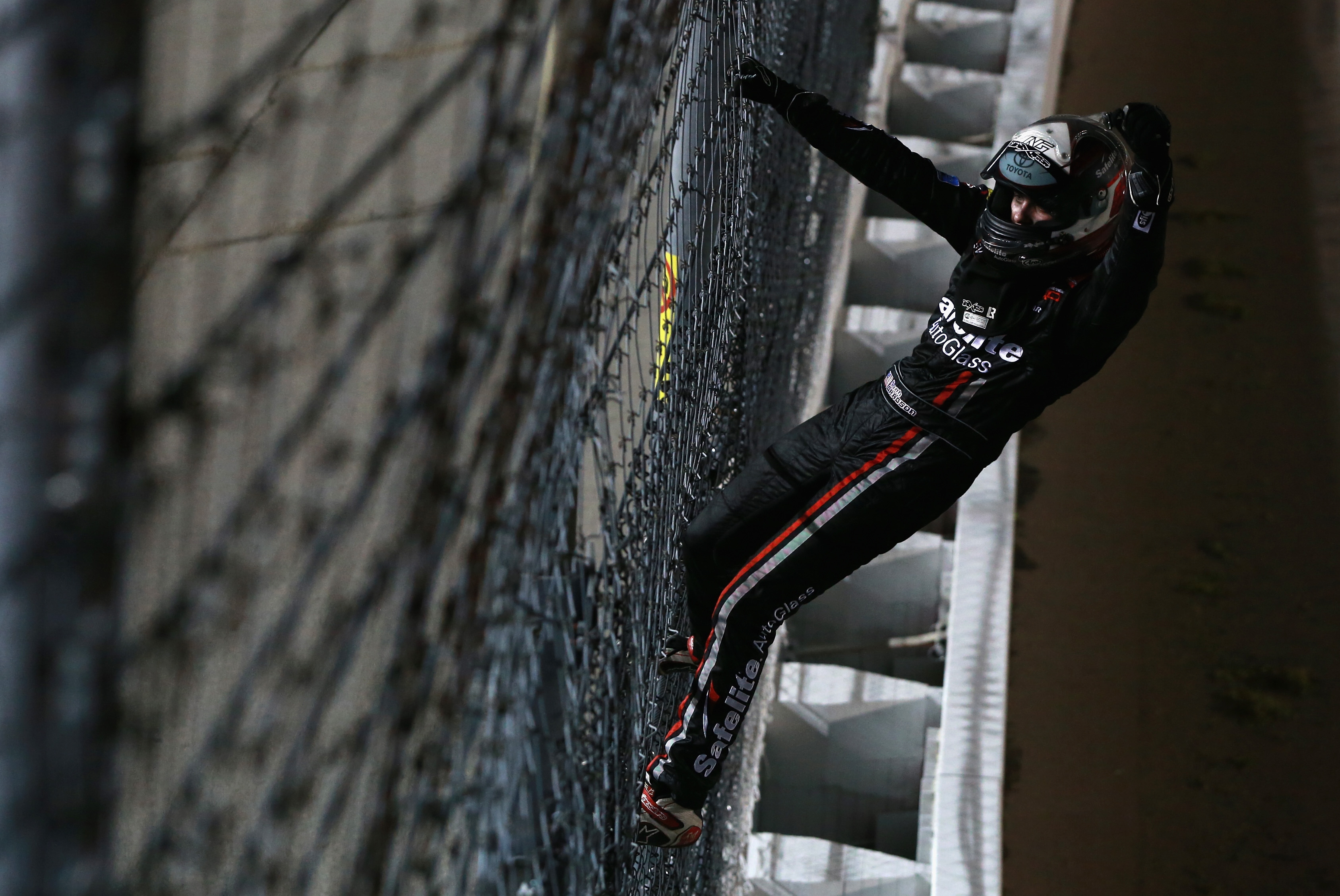Noah Gragson climbs the fence after the win at Kansas Speedway