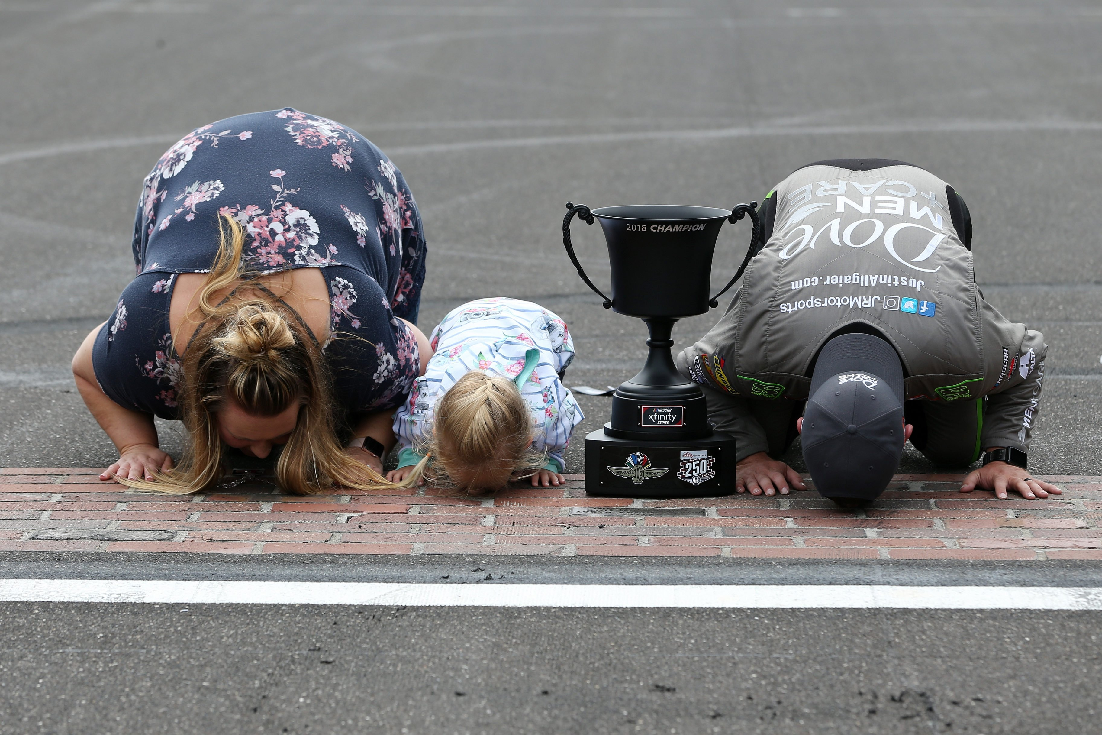 Justin Allgaier and family kisses the bricks at Indianapolis Motor Speedway