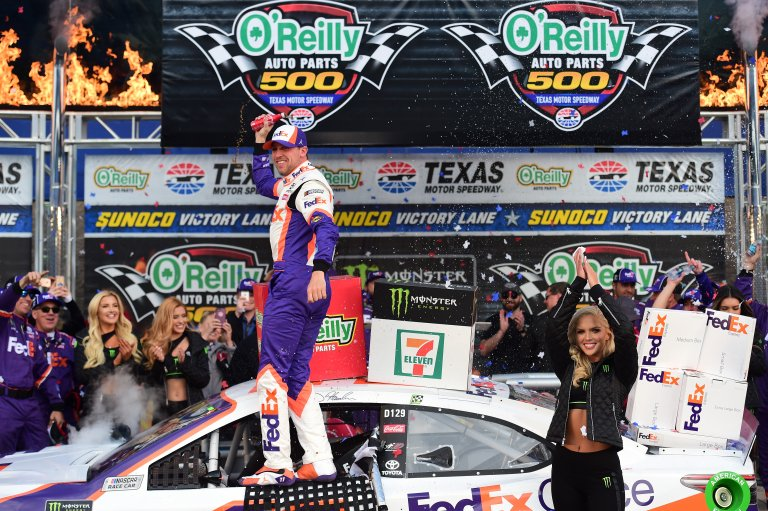 Denny Hamlin in NASCAR victory lane with the Monster Energy Girls