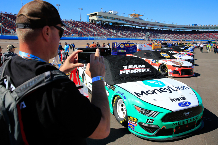 NASCAR fan takes pictures ahead of the start at ISM Raceway