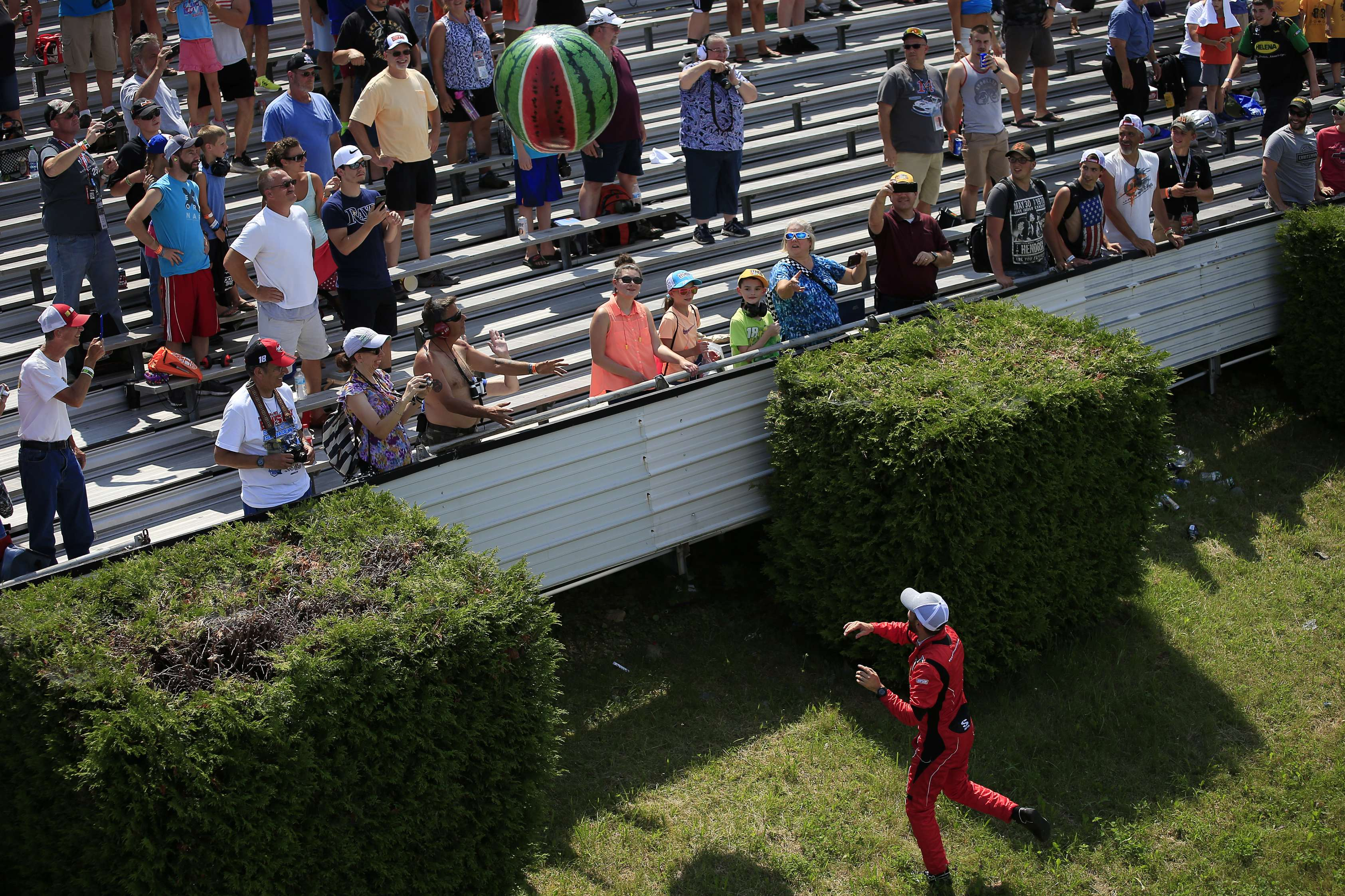 Ross Chastain throws a watermelon beach ball into the crowd at Pocono Raceway