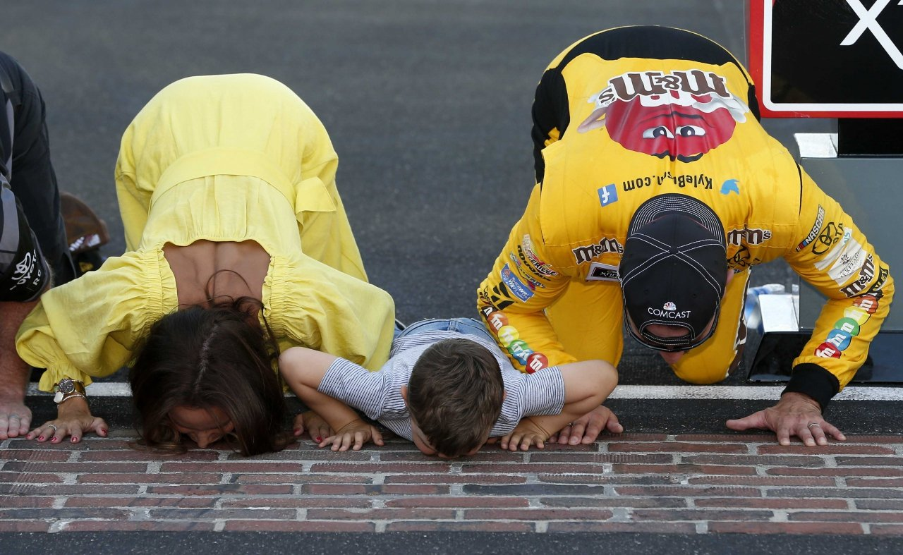 Kyle Busch, Samanthan Busch and Brexton Busch kiss the bricks at Indianapolis Motor Speedway