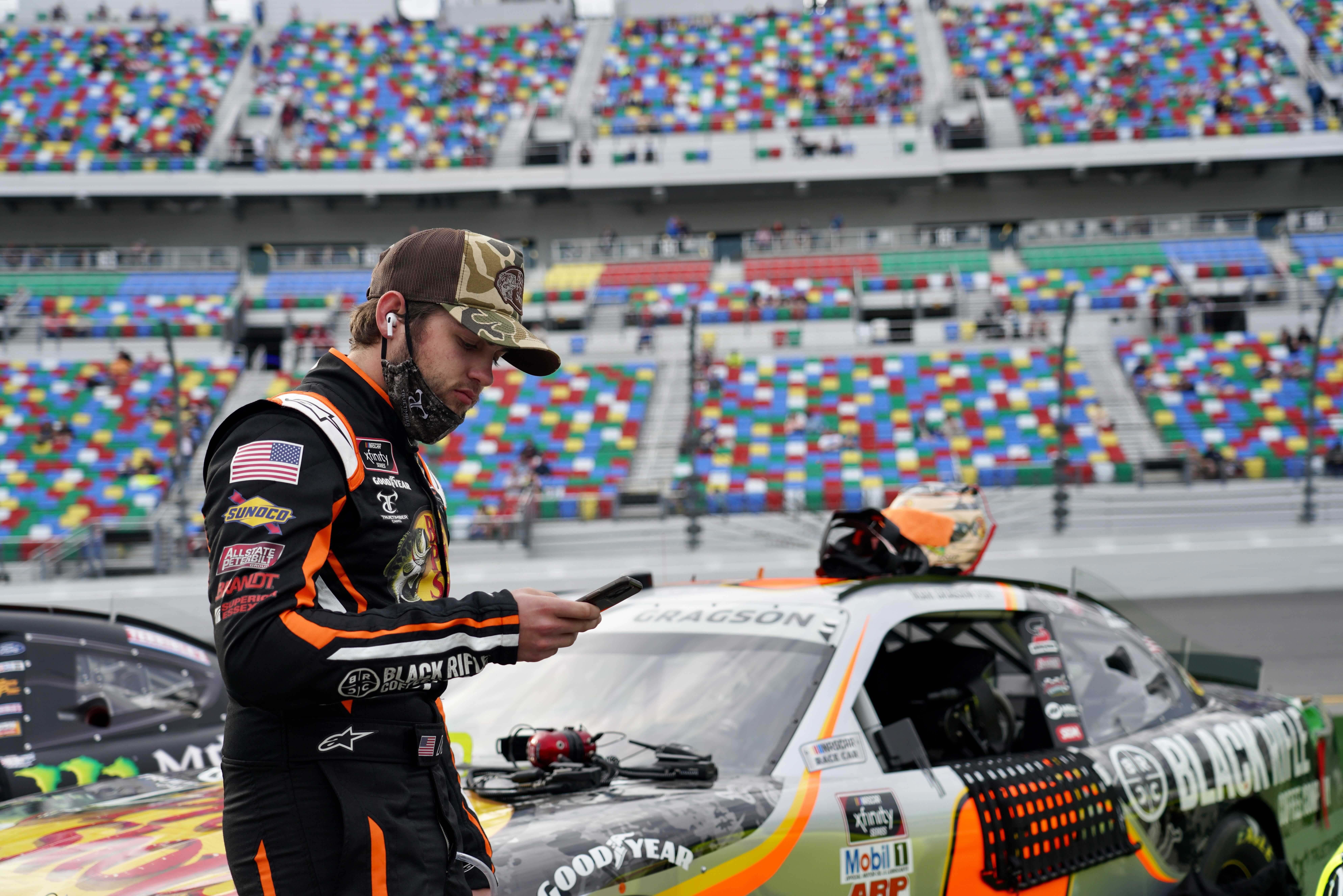 Noah Gragson on his phone at Daytona International Speedway - NASCAR Xfinity Series